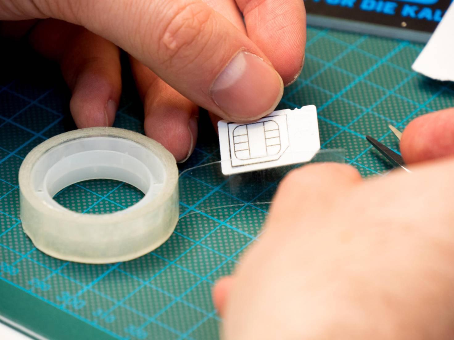 Die Schablone muss zunächst ausgeschnitten und dann auf die SIM-Karte geklebt werden