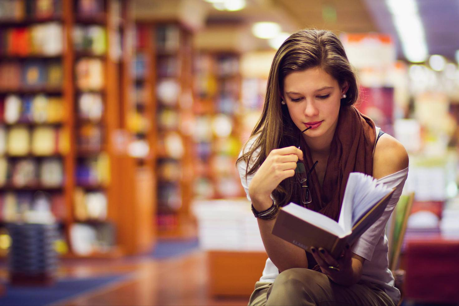A girl is reading among books.