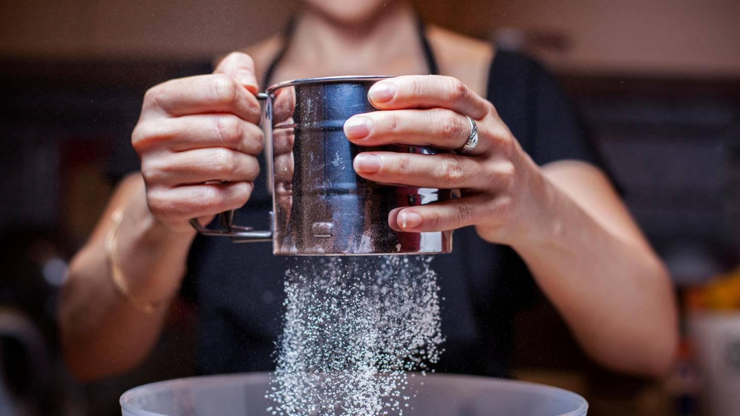 Mit einem Puderzuckersieb bekommst Du den Zucker im Handumdrehen locker. Ein kleines Küchensieb tut's aber auch.