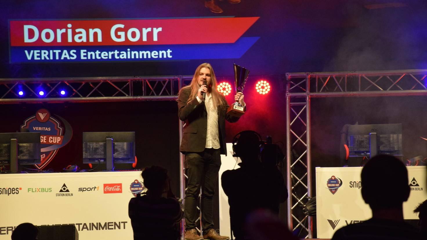 """Veranstalter Dorian Gorr mit dem Pokal, um den die Teams beim """"Veritas College Cup"""" spielen."""