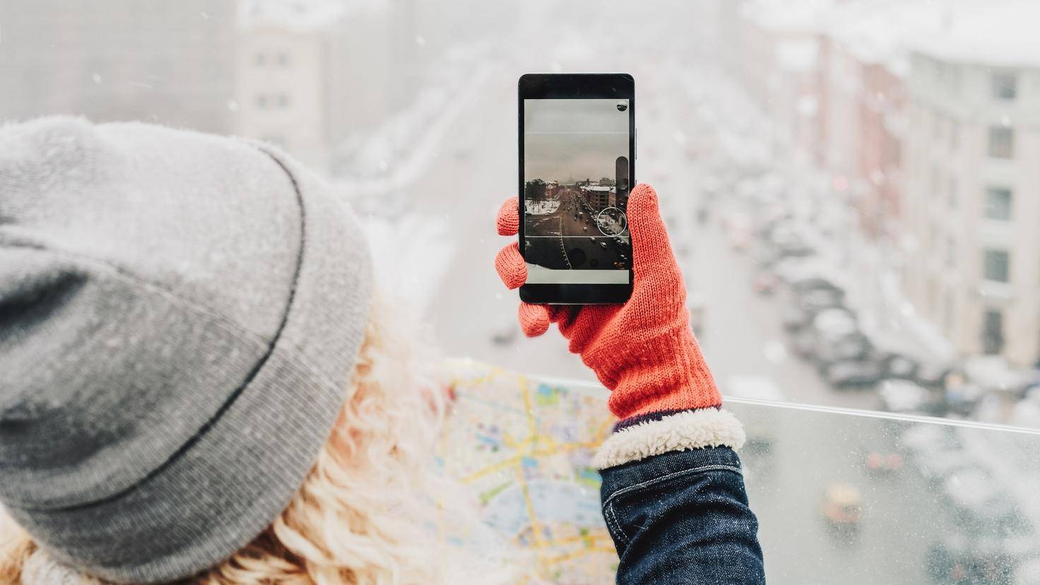 Curly blond girl making photo on her smartphone