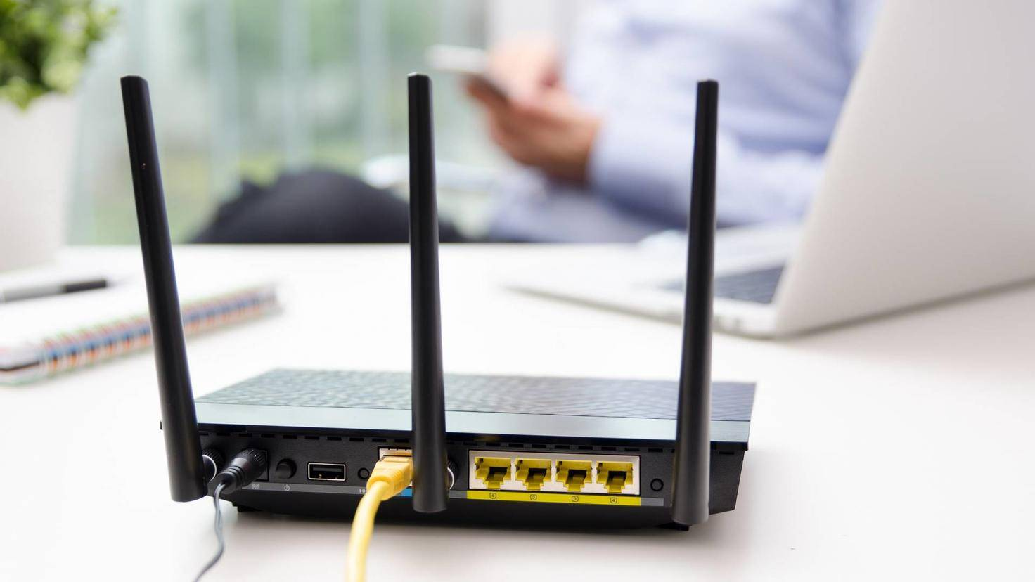Wireless router and man using a smart phone in home