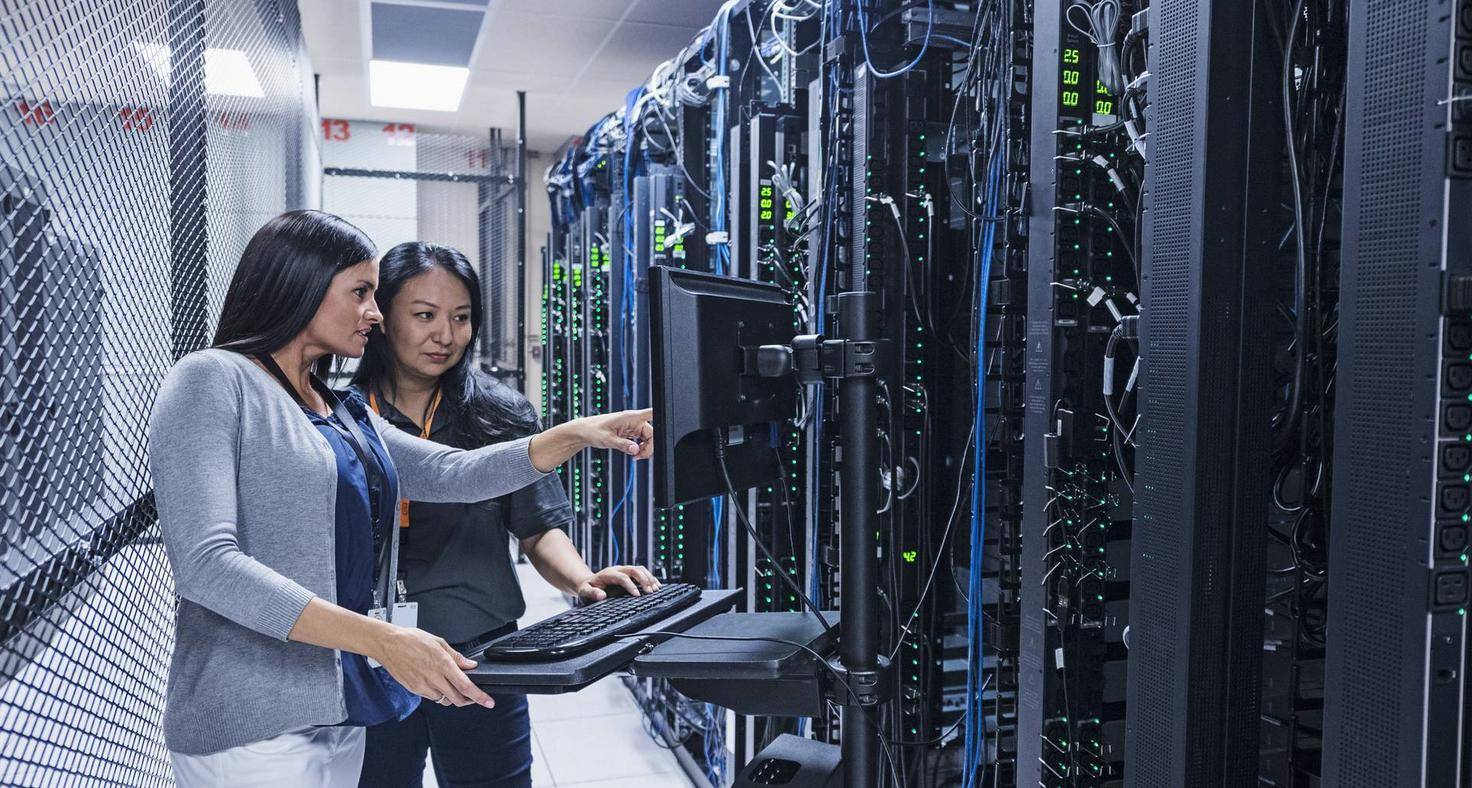 Two women working with computer in server room
