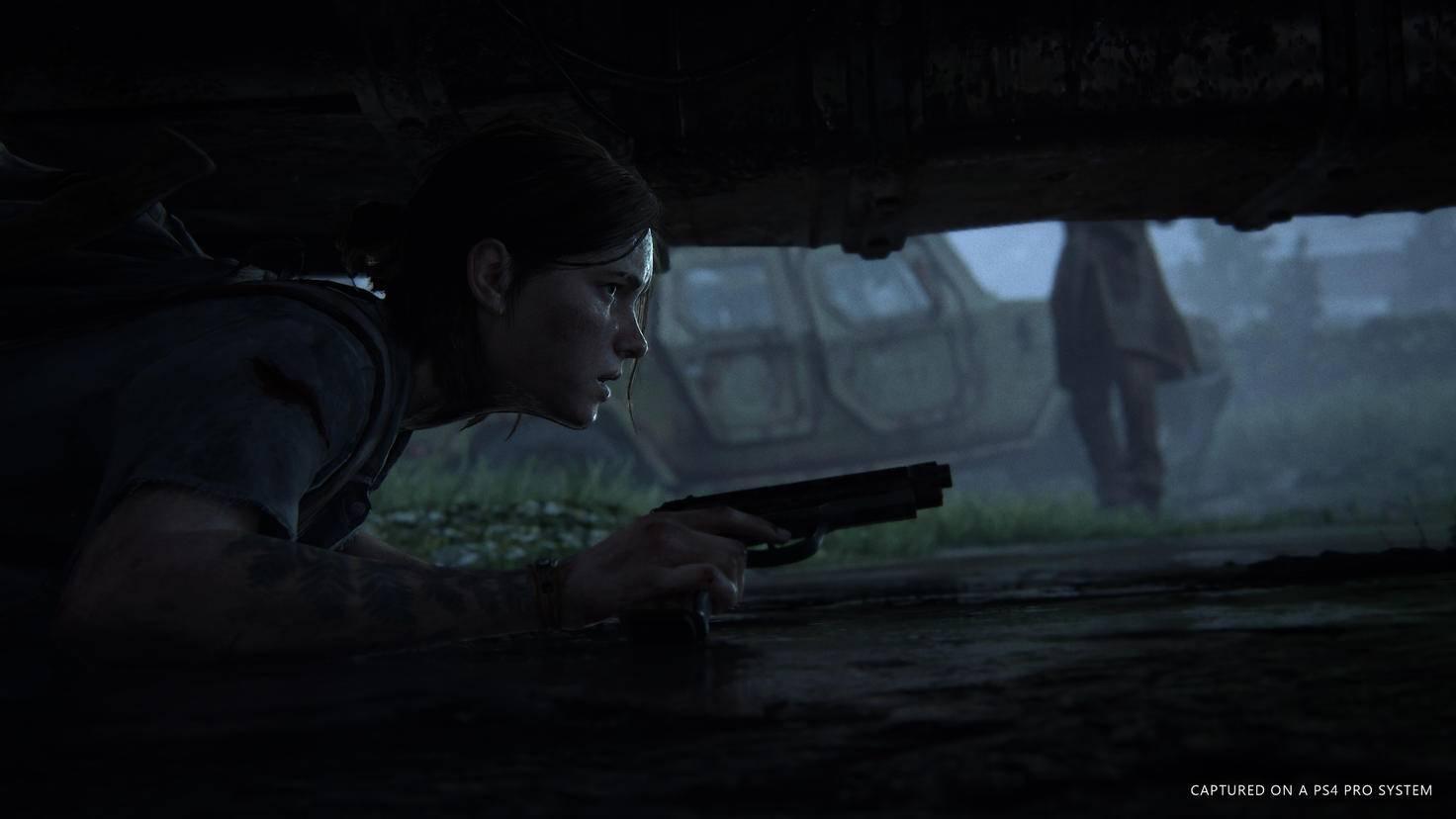 """Gut versteckt unter einem Auto wartet Ellie, bis die Luft wieder rein ist – ein neues Stealth-Feature in """"The Last of Us 2""""."""