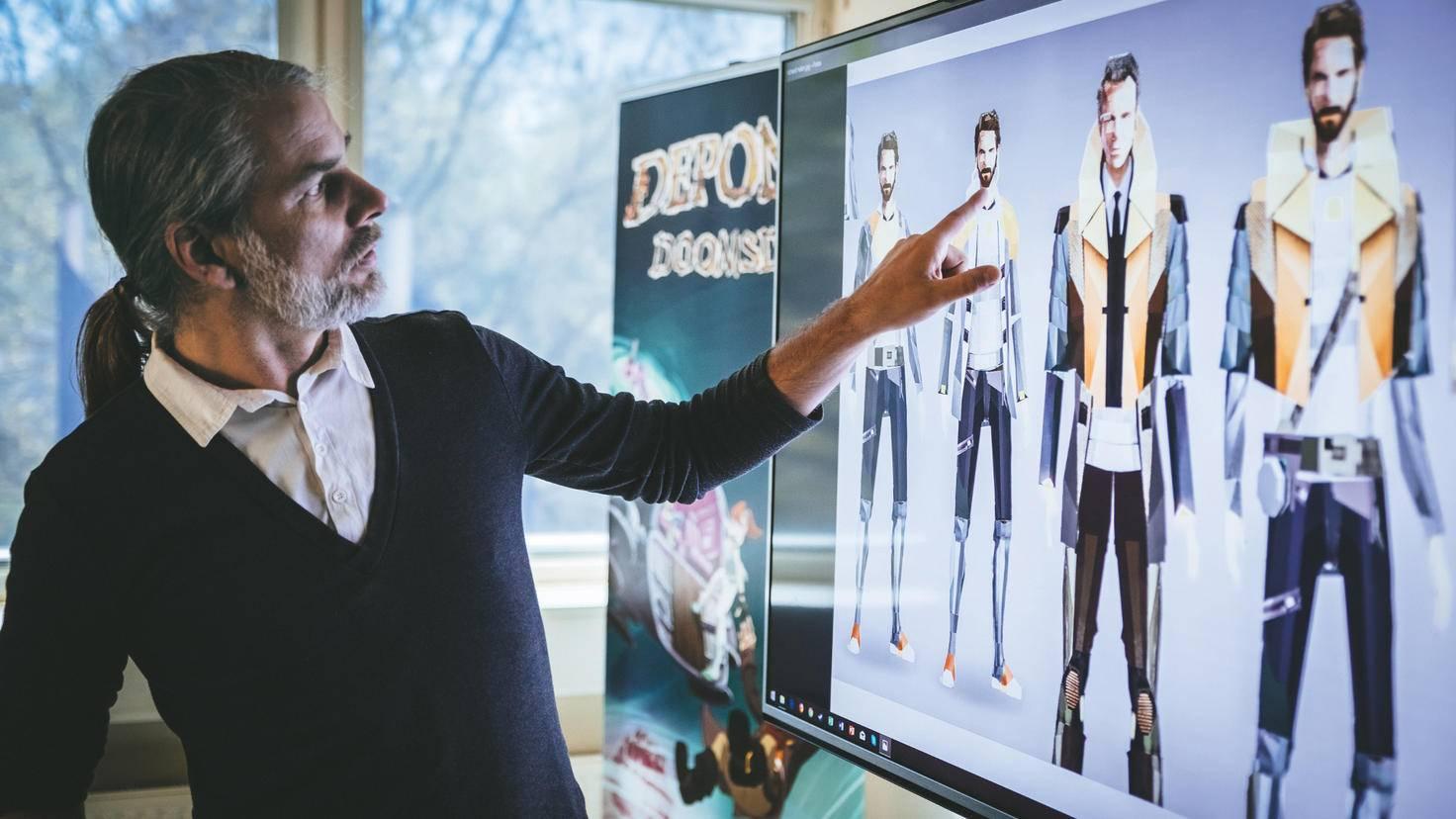 """Kai Fiebig, Head of Production bei Daedalic, präsentiert verschiedene Layouts zu Richard Nolan, der Titelfigur im neuen Game """"State of Mind"""". Zweieinhalb Jahre dauerte die Produktion."""