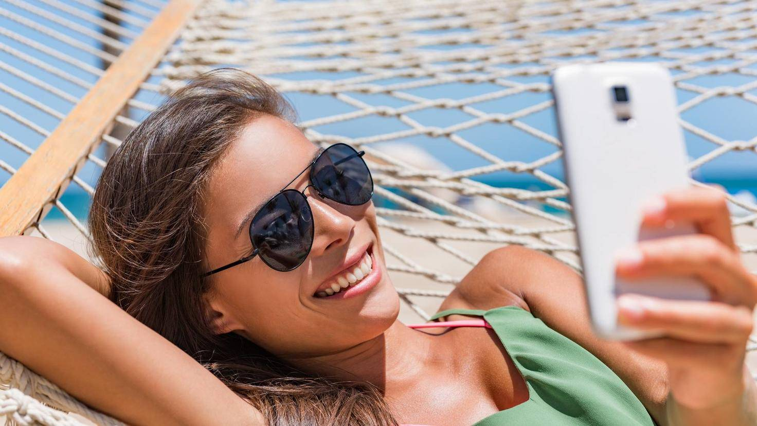 Vacation woman using smart phone taking smartphone selfie. Girl relaxing on beach hammock sun tanning in sunglasses smiling using cellphone to take pictures and text sms messages.