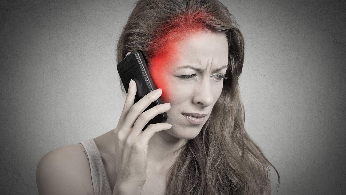 Side profile girl on the phone with headache red area of pain