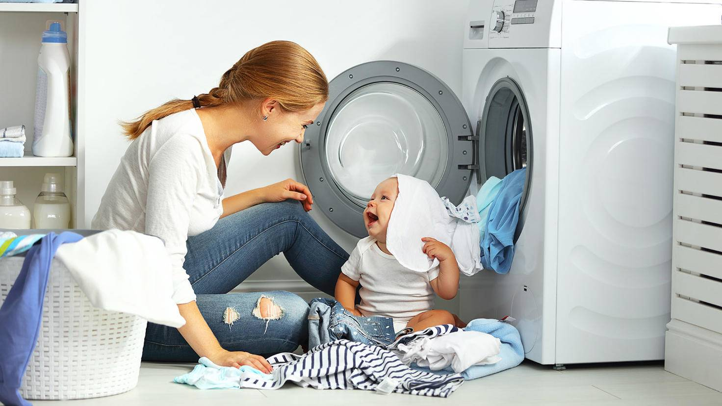 Mutter wäscht mit Baby zusammen Kleidung