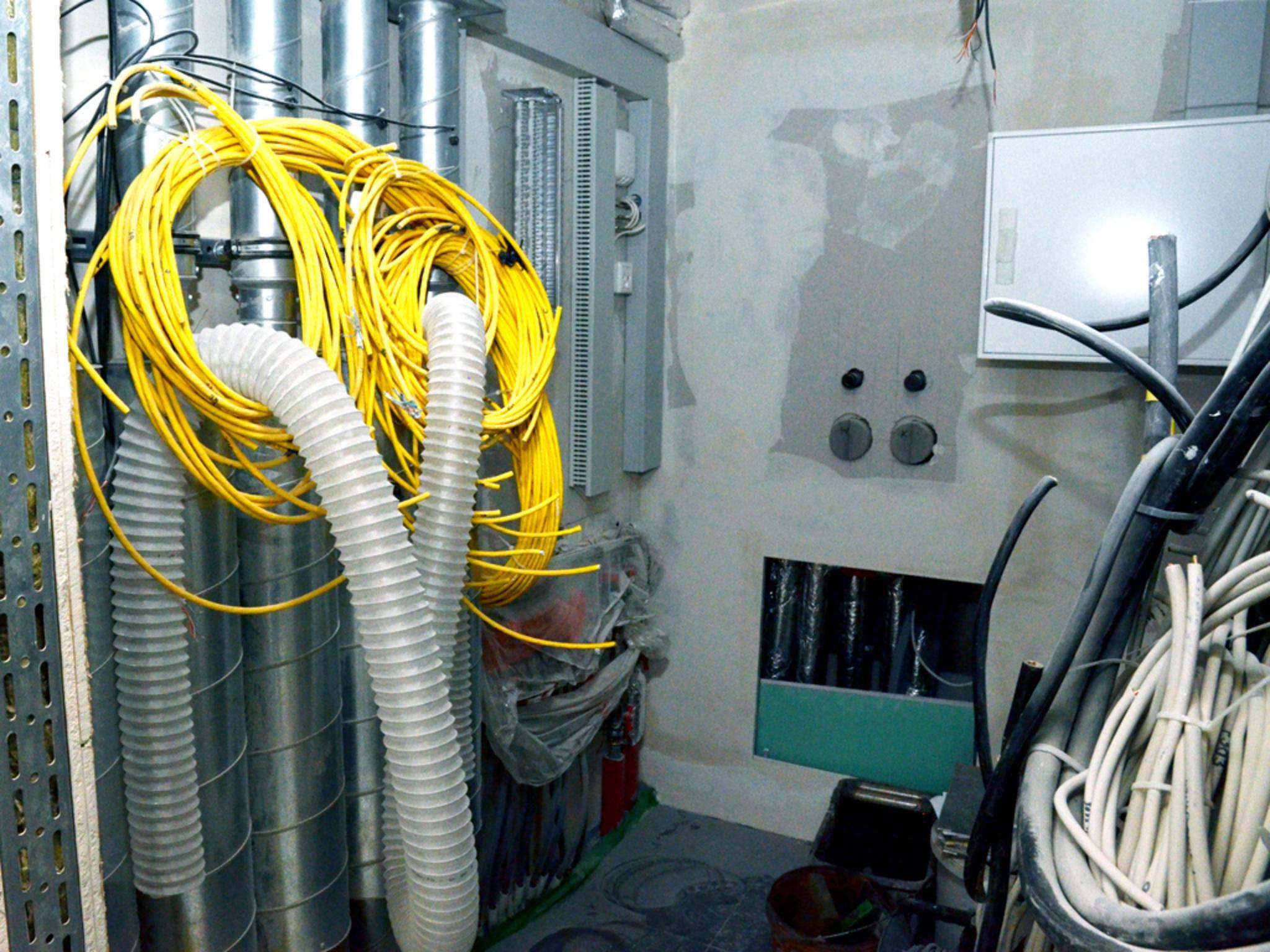 Überall sind dicke Kabelstränge mit gelben Netzwerkkabeln verlegt, die ...