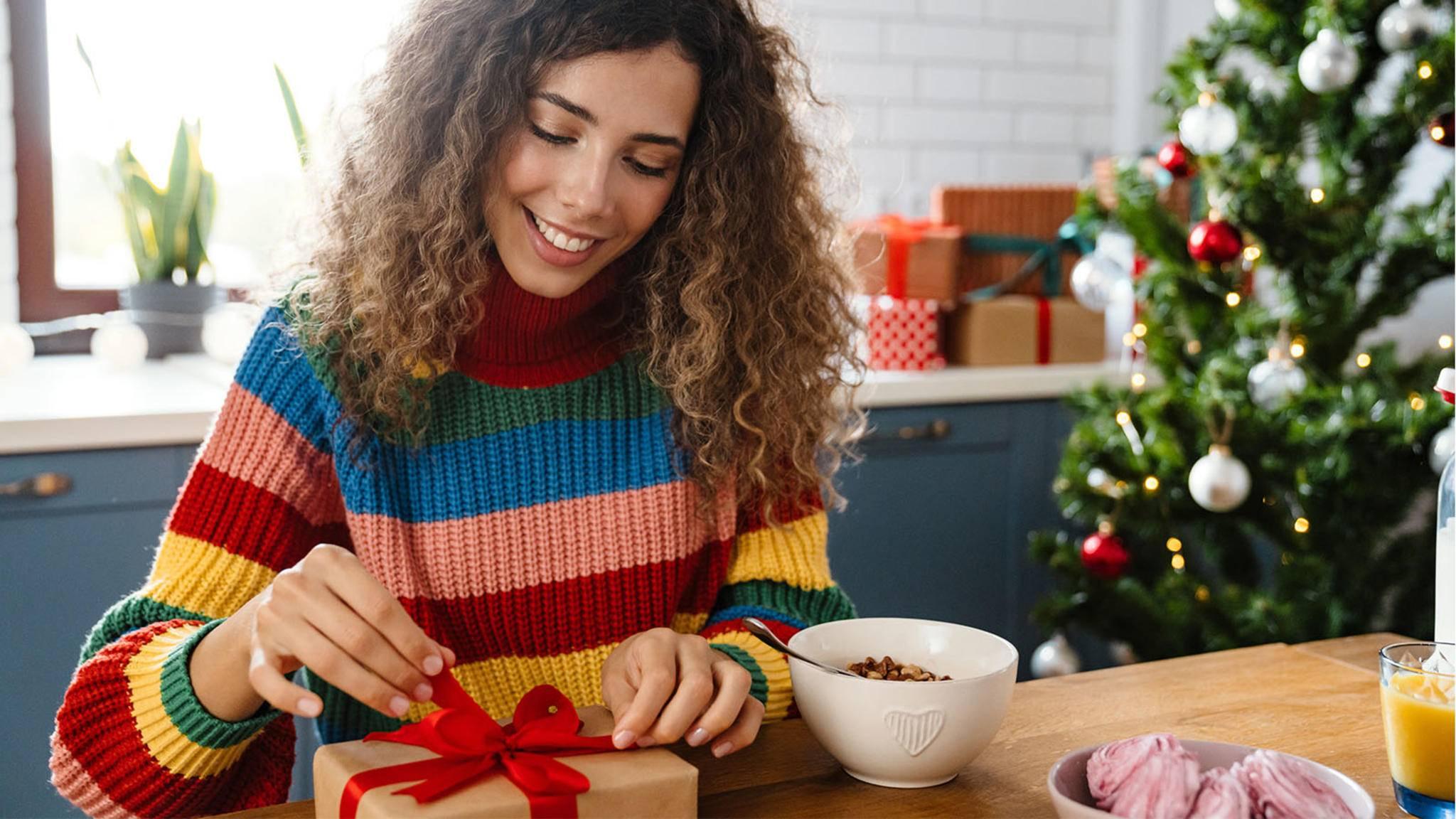 Frau öffnet Weihnachtsgeschenk in Küche am Tisch