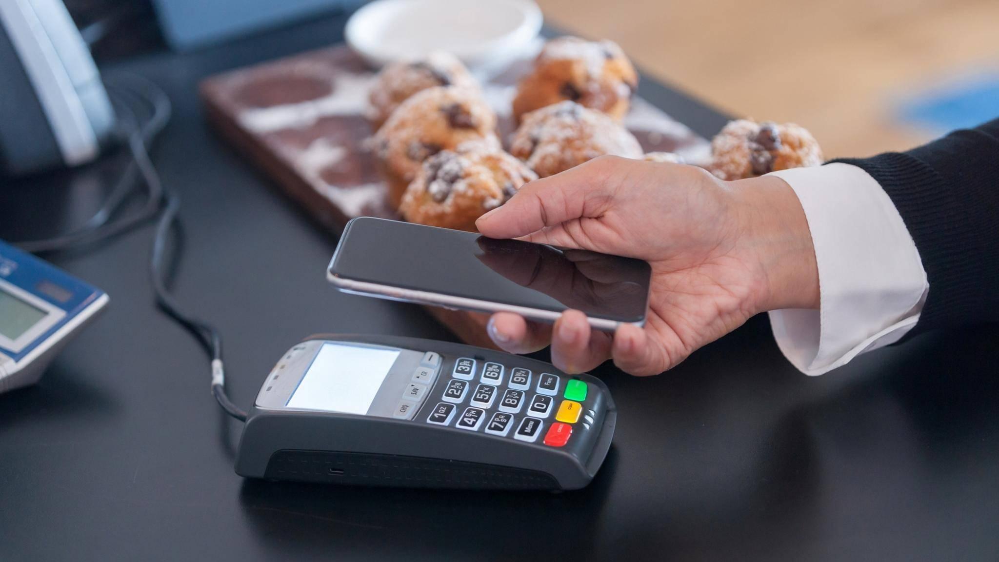 iPhone dicht an das Terminal halten und mit Touch ID die Zahlung bestätigen – so funktioniert Apple Pay in Geschäften.