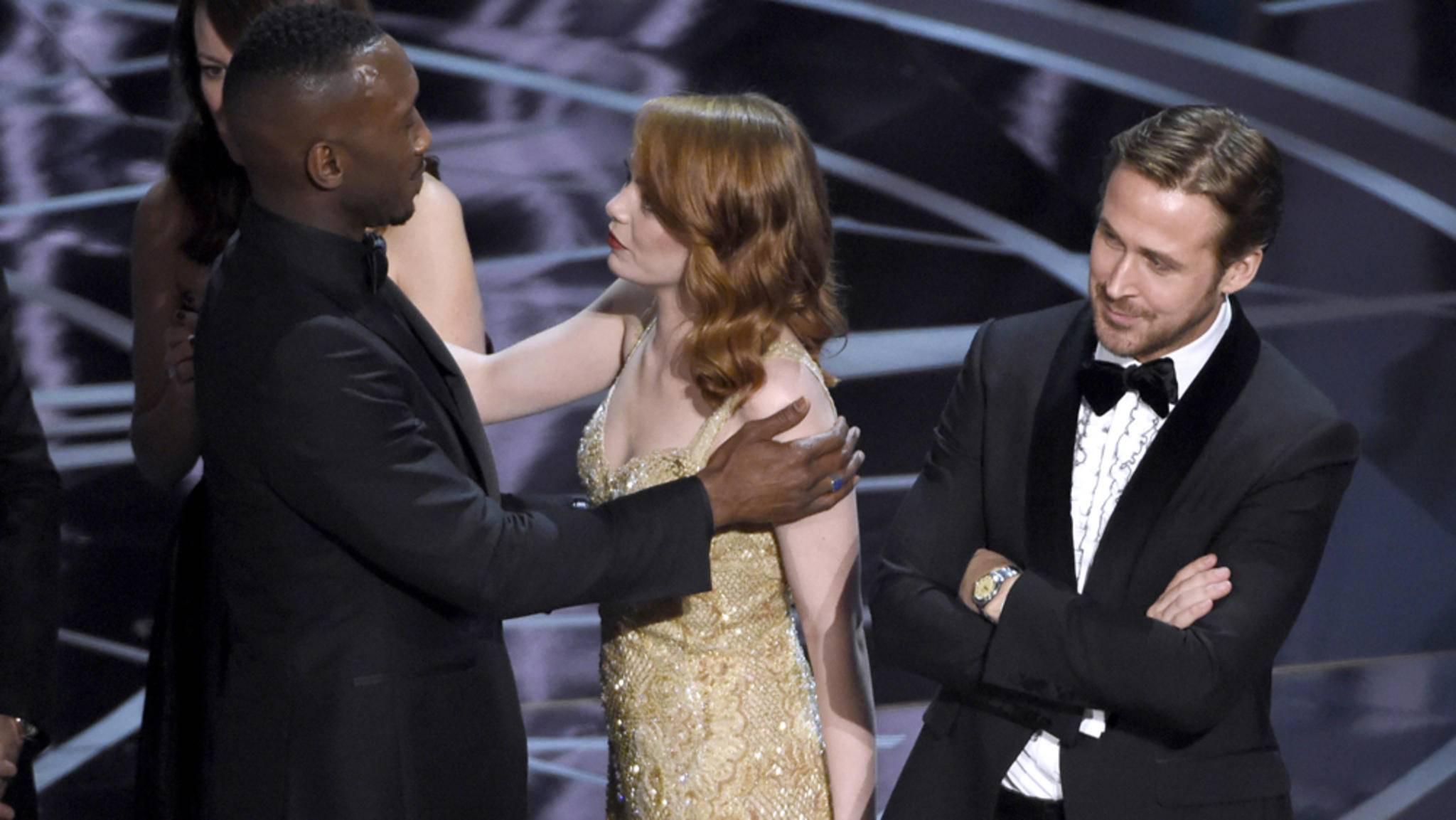 """Blöde Panne: """"Moonlight""""-Darsteller Mahershala Ali tröstet Emma Stone, die plötzlich doch nicht mehr im besten Film des Jahres mitgespielt hatte. """"La La Land""""-Hauptdarsteller Ryan Gosling schaut auch nicht so ganz glücklich."""