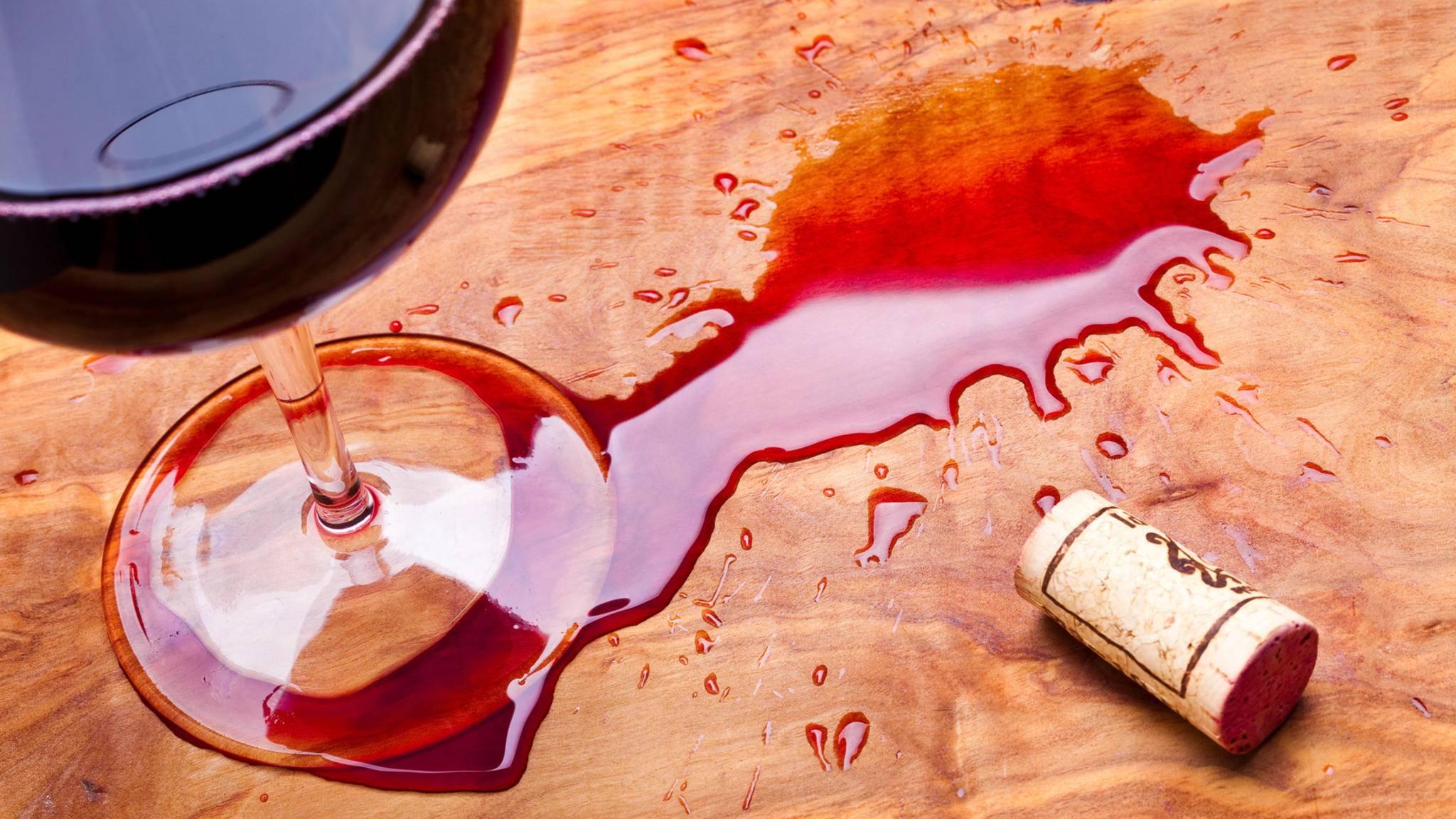 Leicht ist Rotwein verschüttet: Während er sich von der Tischplatte noch leicht entfernen lässt, solltest Du bei Flecken auf der Kleidung schnell handeln.