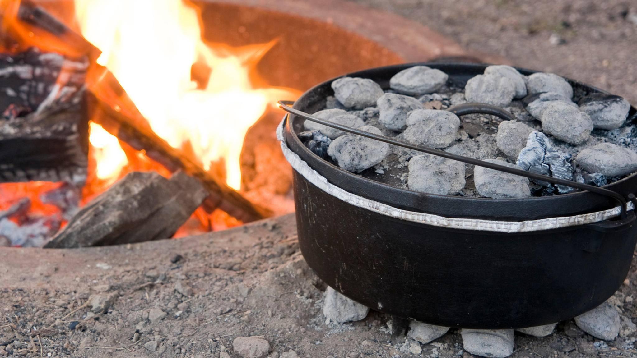 Heiße Kohlen unter dem Boden und auf dem Deckel sorgen beim gusseisernen Dutch Oven für gleichmäßige Hitze.