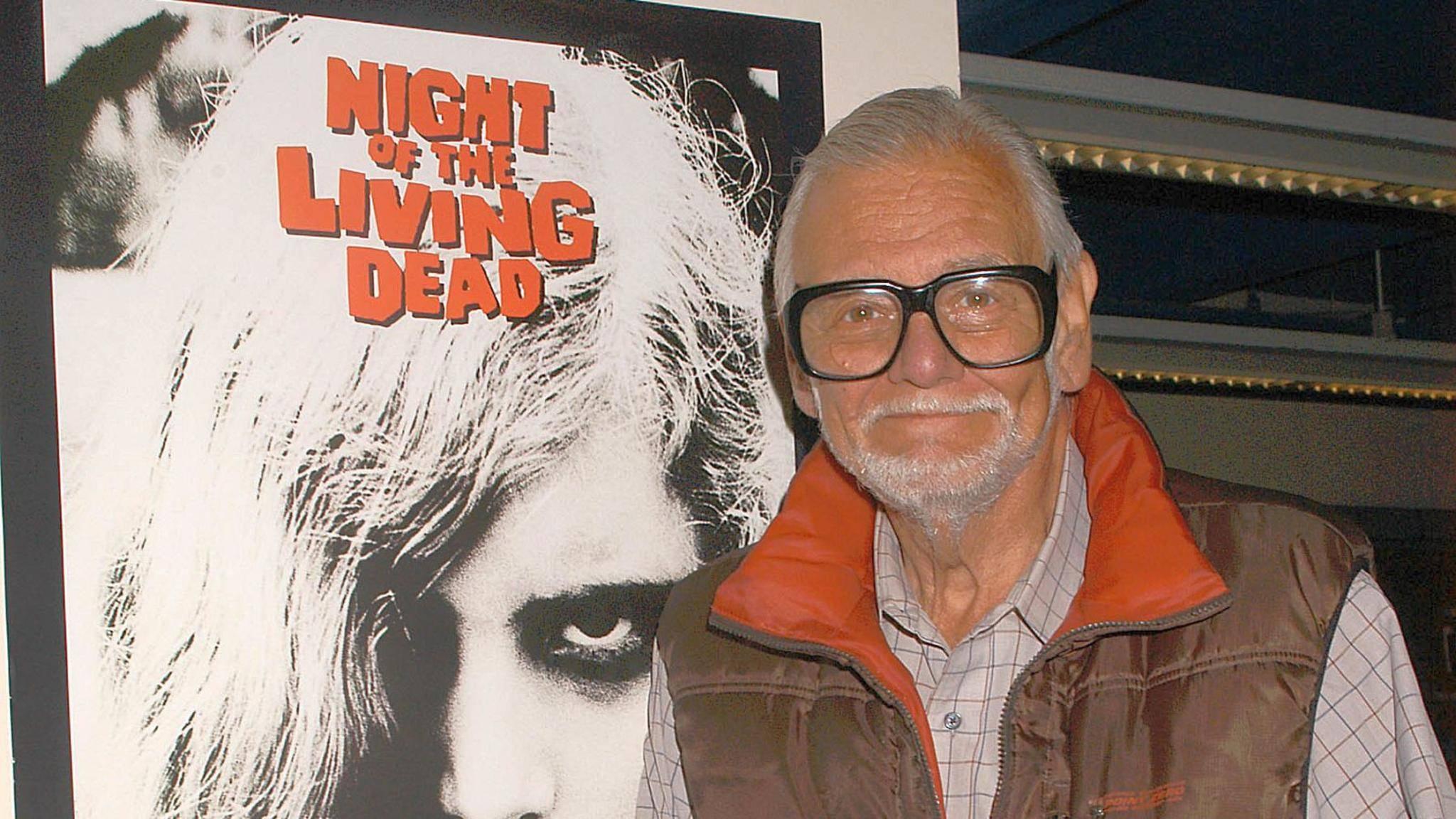 """Der Meister der Untoten: George A. Romero posiert neben einem Poster seines Durchbruch-Films, """"Die Nacht der lebenden Toten""""."""