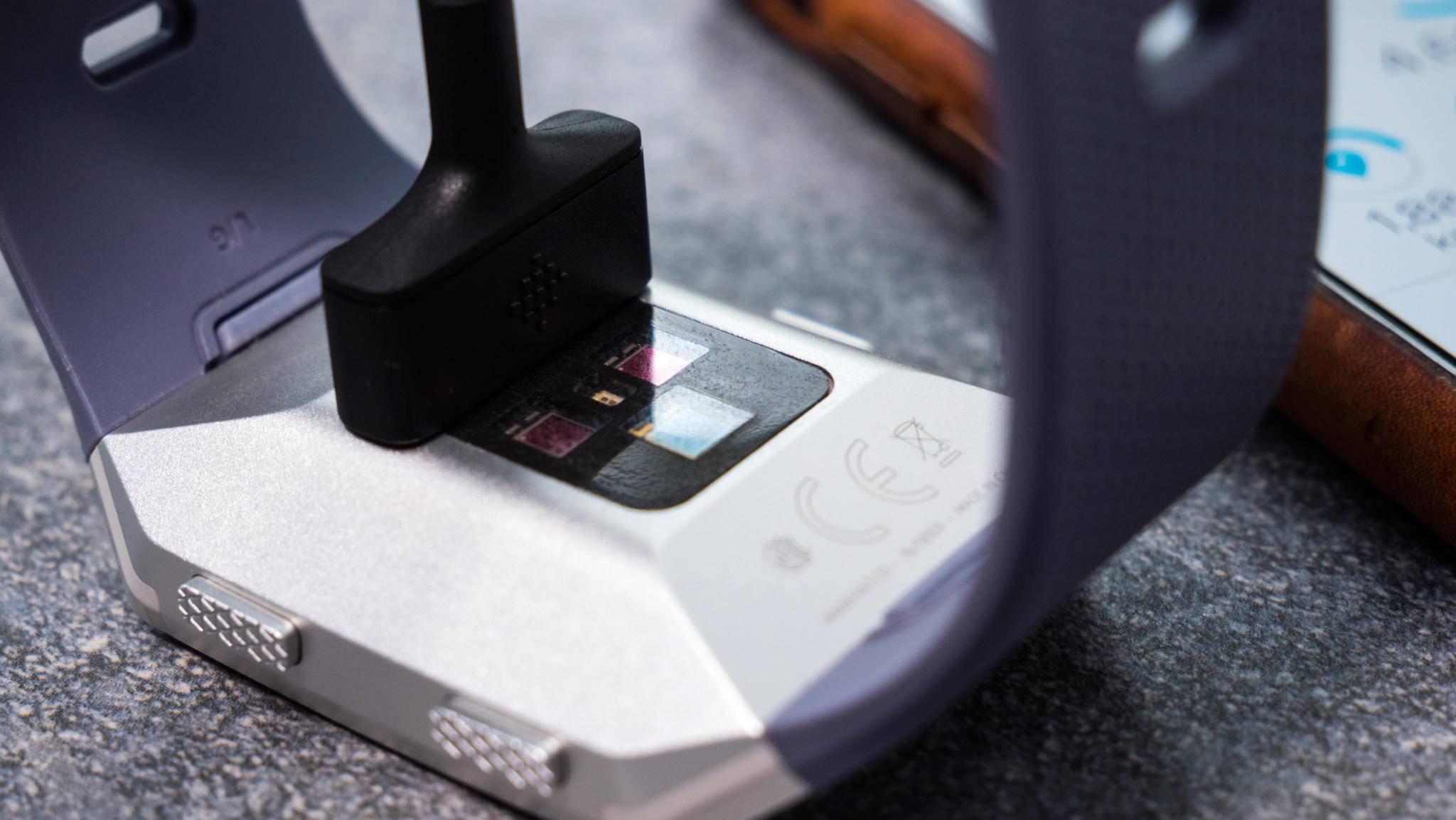 Mithilfe eines kleinen Magneten wird das Ladekabel an der Rückseite der Fitbit Ionic befestigt.