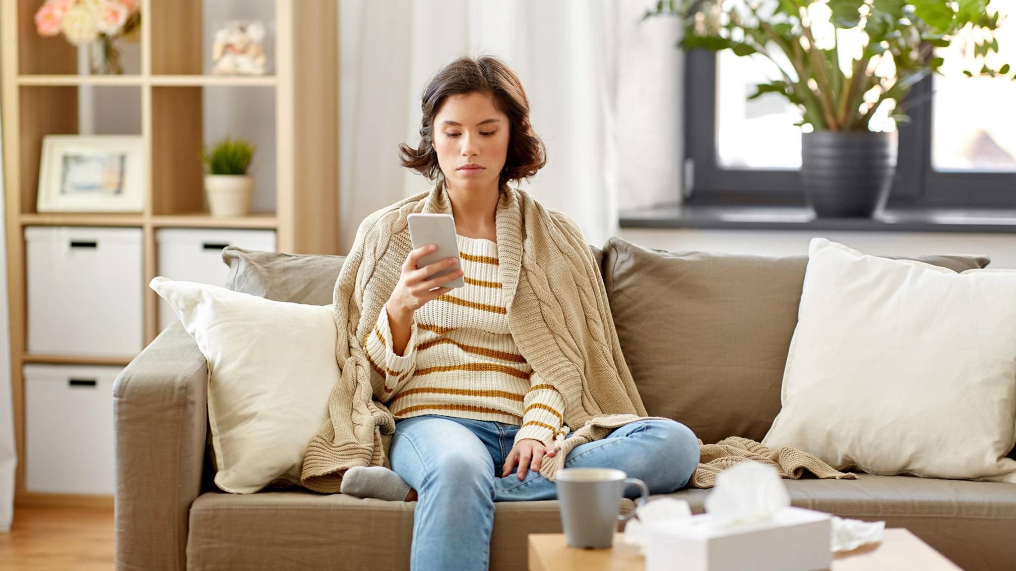 frau krank smartphone wohnzimmer