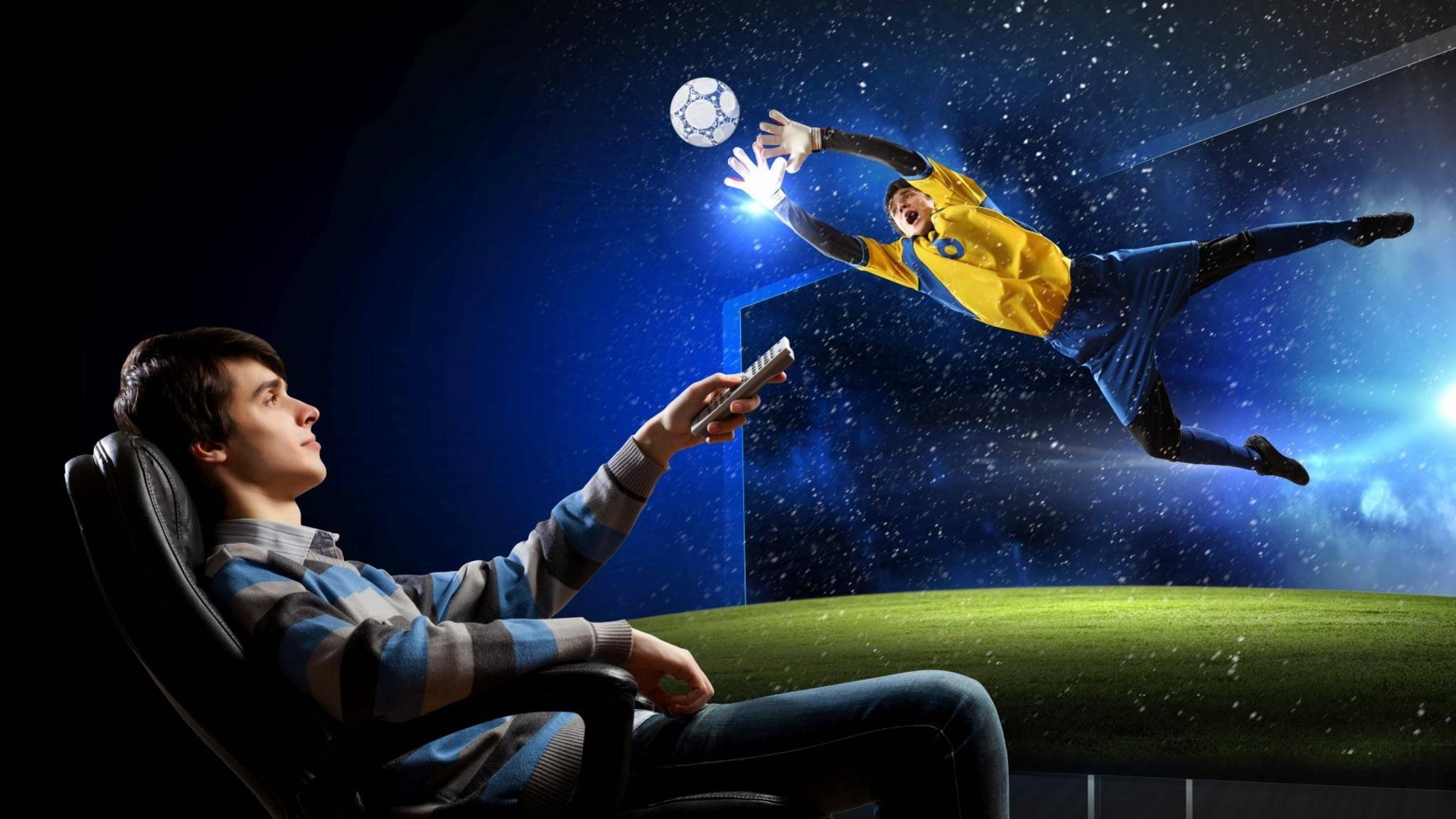 Junger Mann schaut Fußball auf großem Fernseher