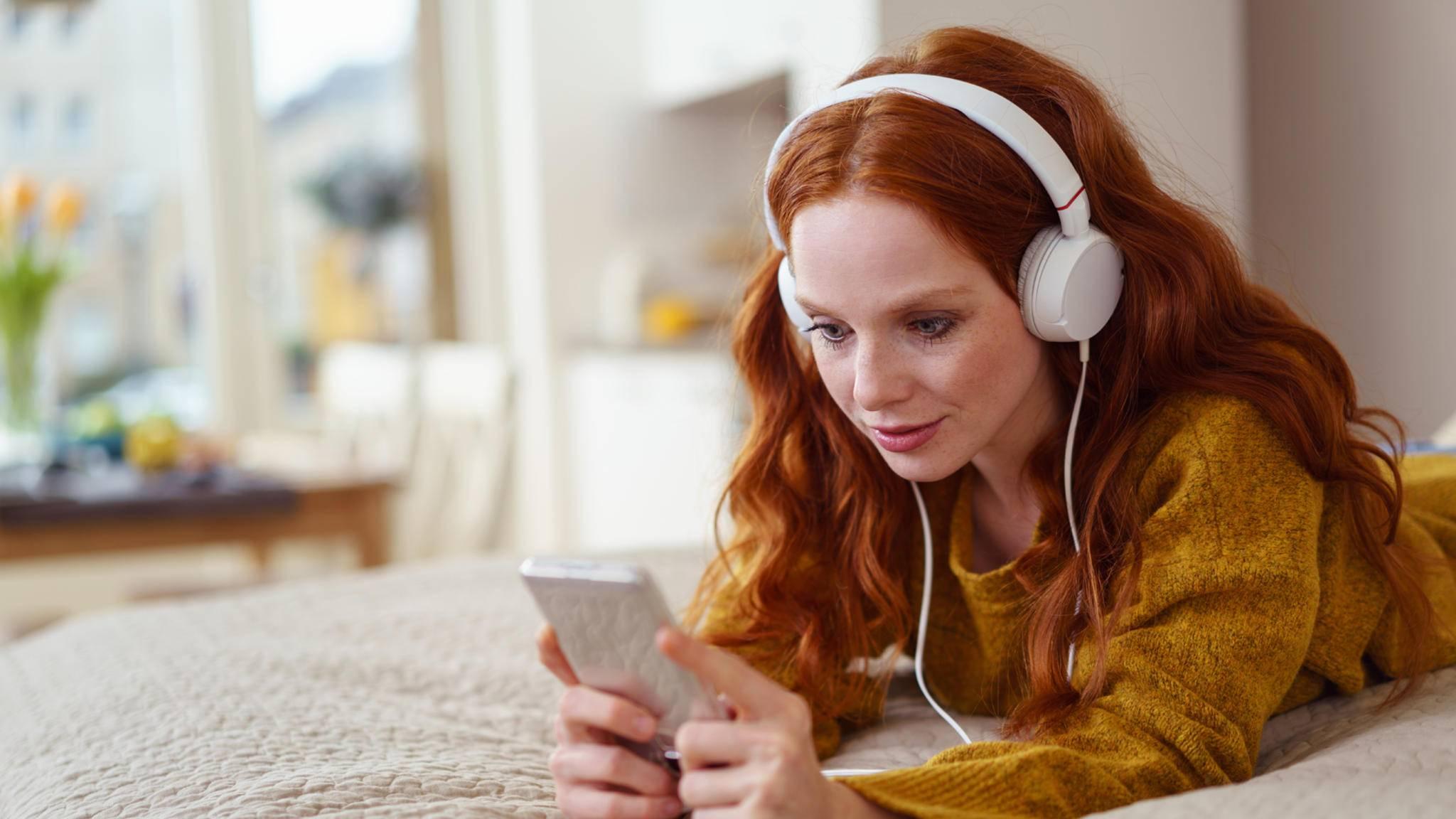 frau smartphone bett musik kopfhörer