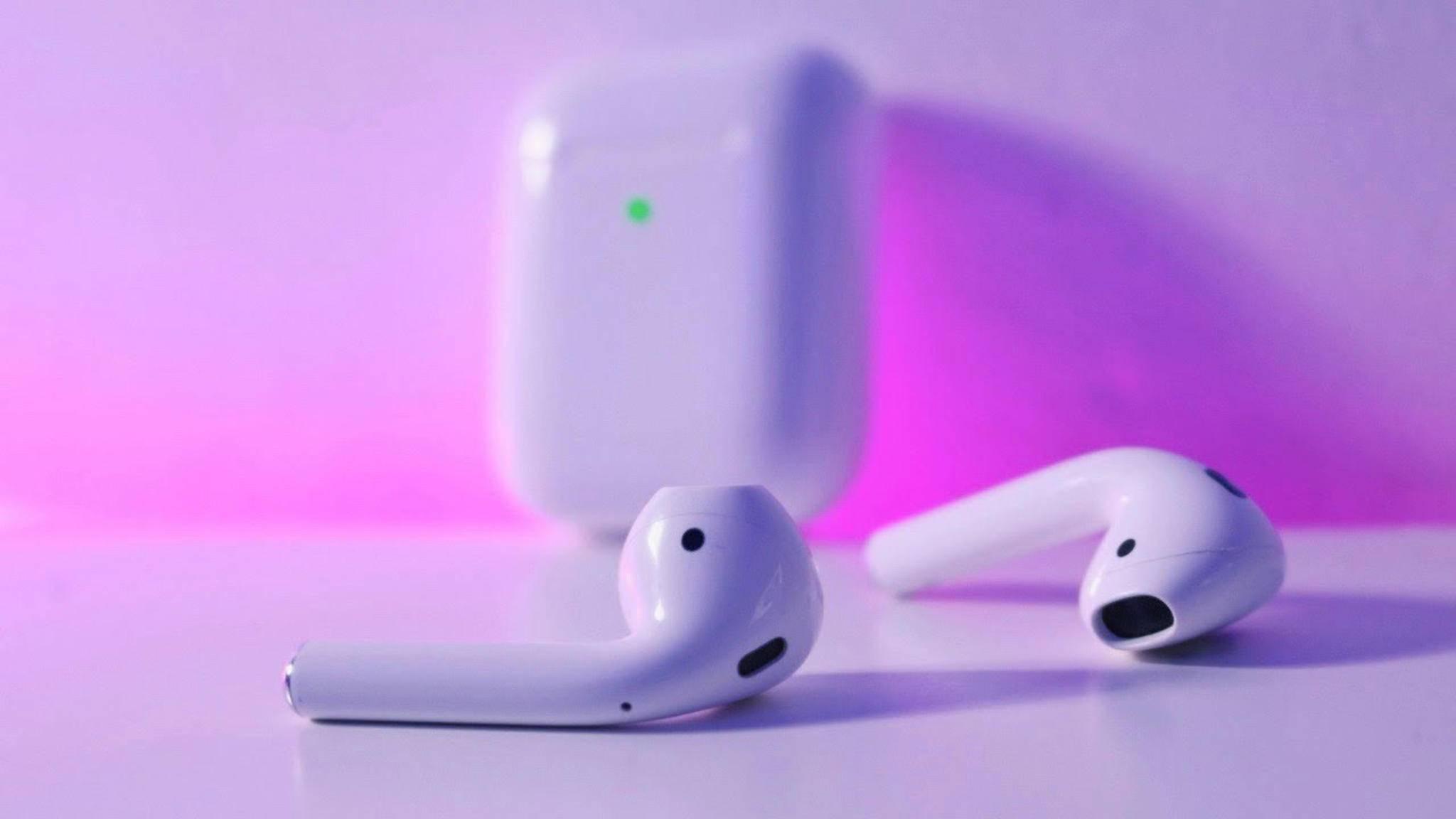 Apple AirPods 2 liegen auf einer Oberfläche, während im Hintergrund das neue Wireless-Charging-Case zu sehen ist.