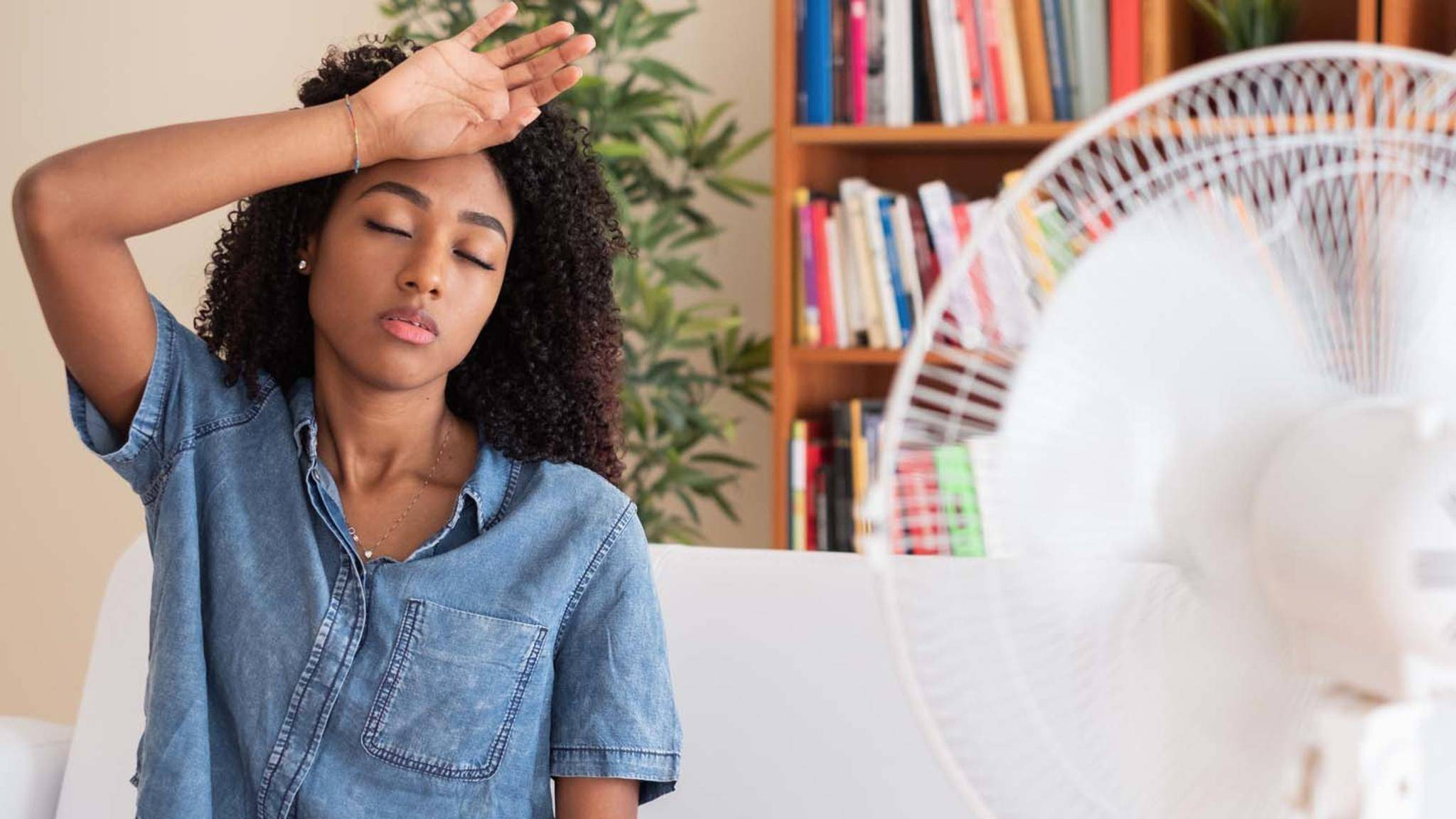 Woman refreshing in front of a fan-Ventilator-Frau-heiß-Paolese-AdobeStock_269986728
