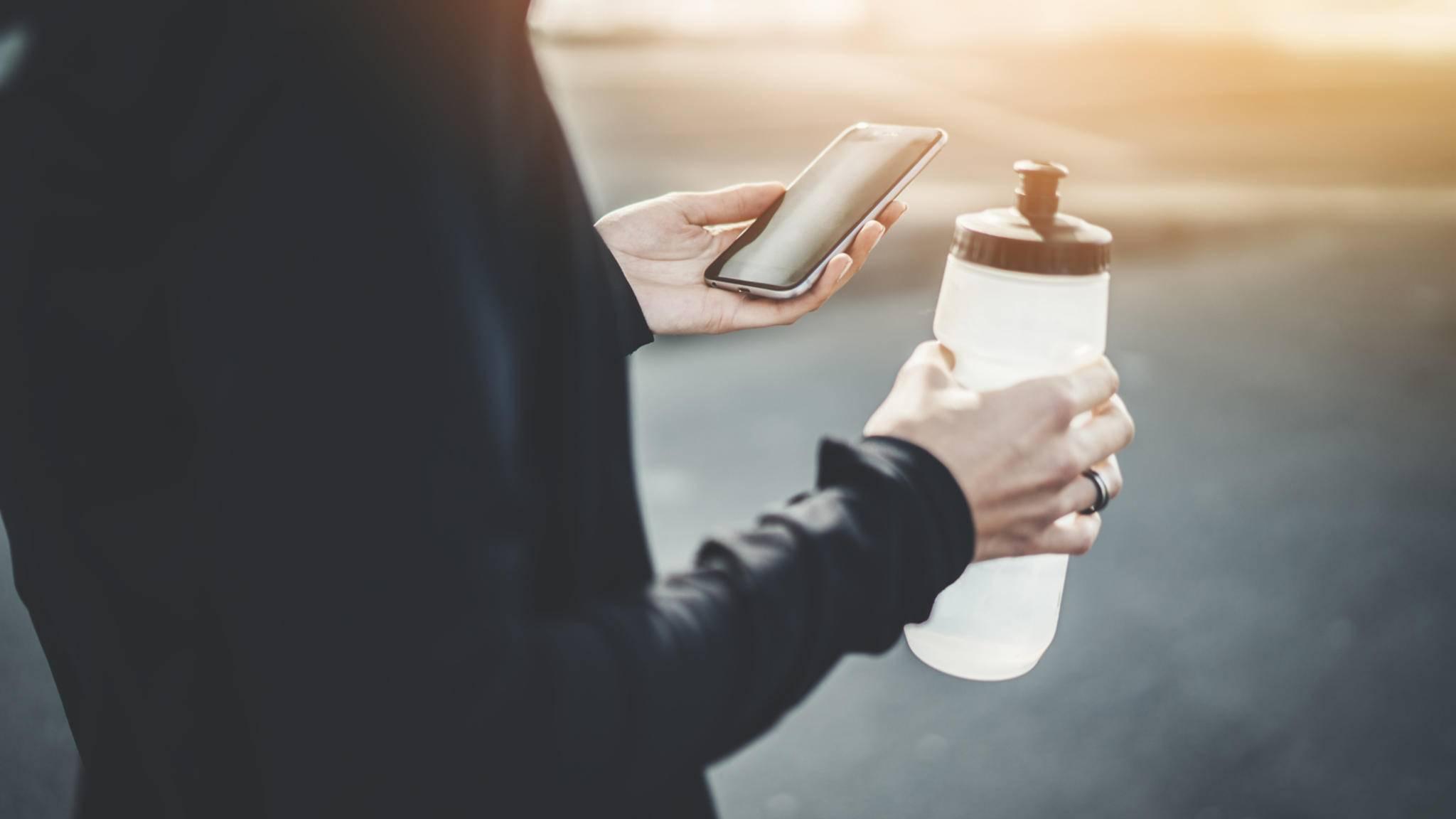 frau smartphone wasserflasche