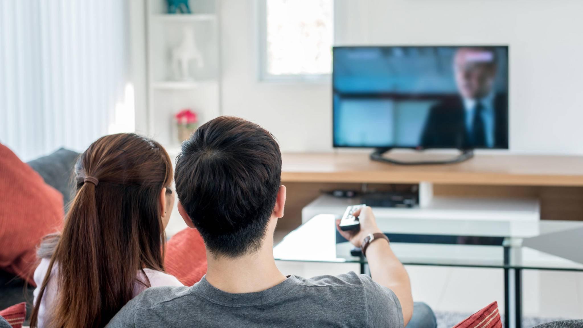 Paar sitzend auf Couch vor Fernseher