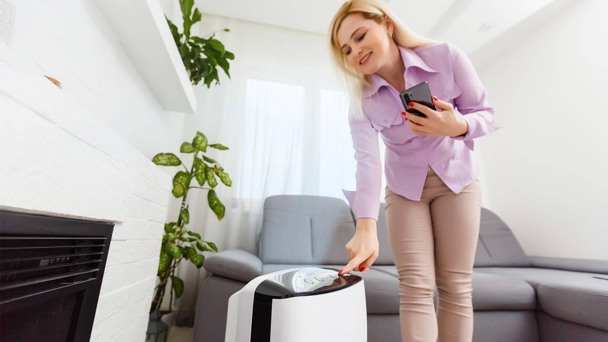 Frau bedient Klimagerät mit Smartphone