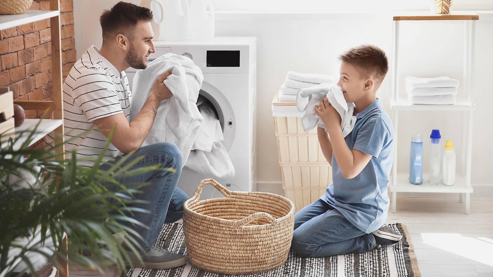 Vater und Sohn waschen Wäsche mit der Siemens iQ700