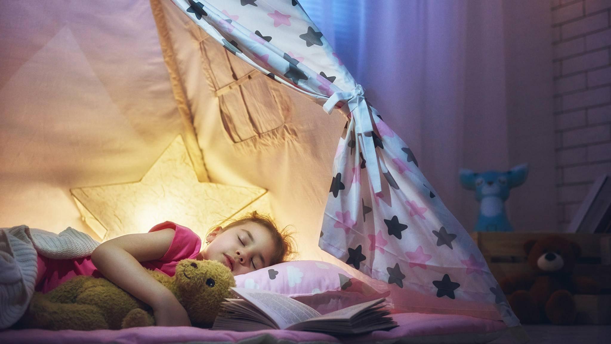 Mädchen schläft mit Nachtlicht im Zelt
