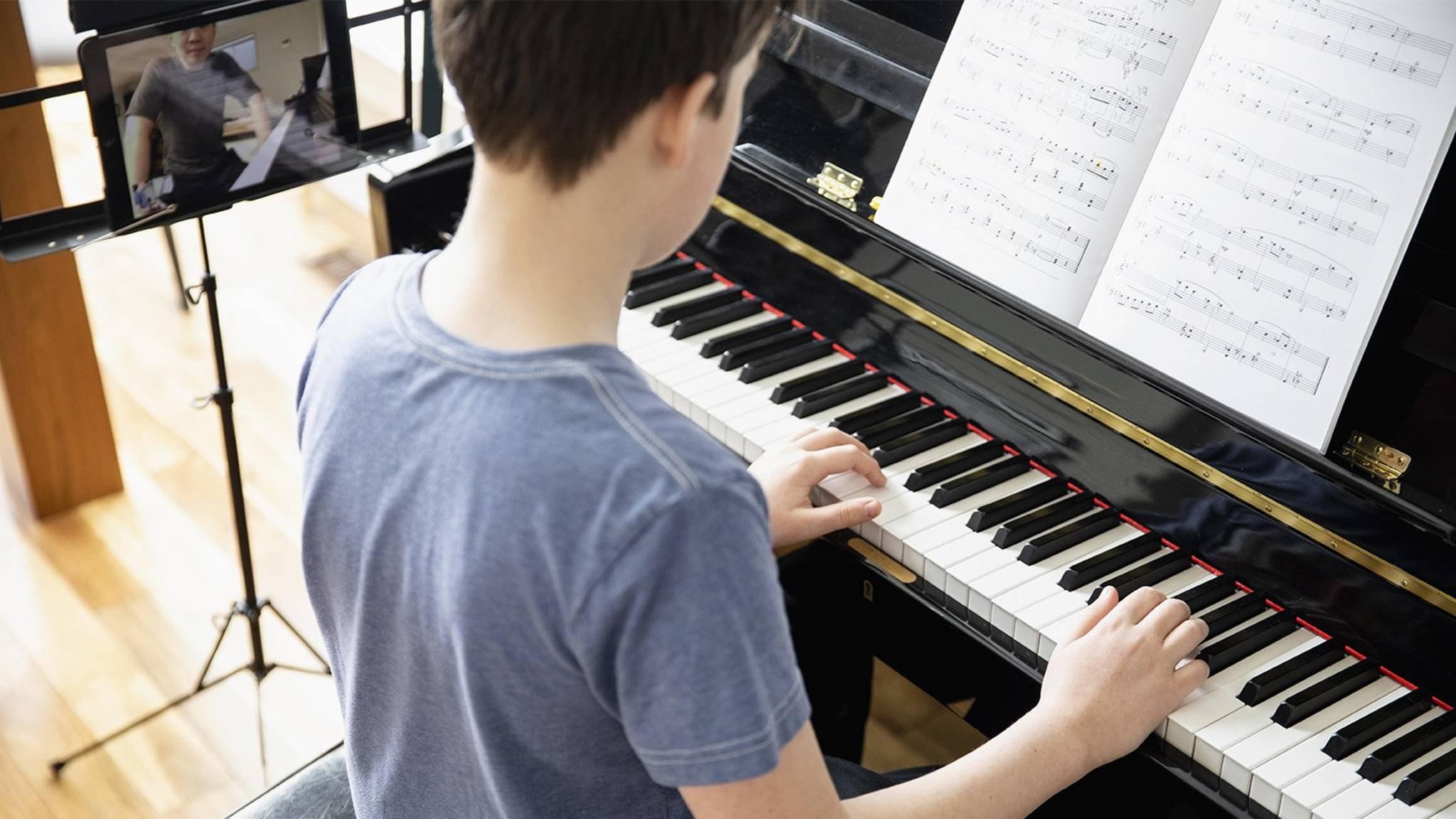 Kind lernt Klavier online mit Tablet