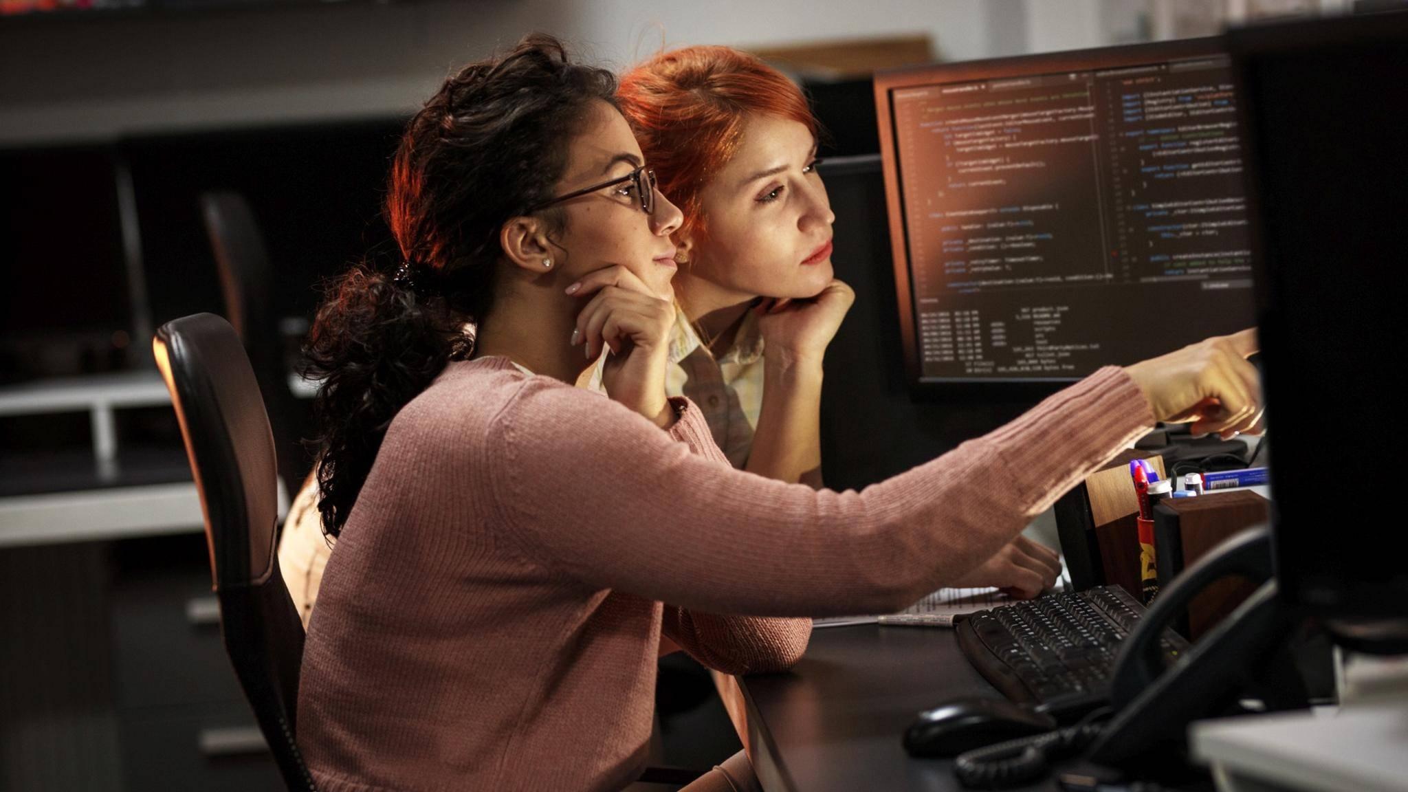 Zwei Frauen arbeiten am PC mit mehreren Monitoren