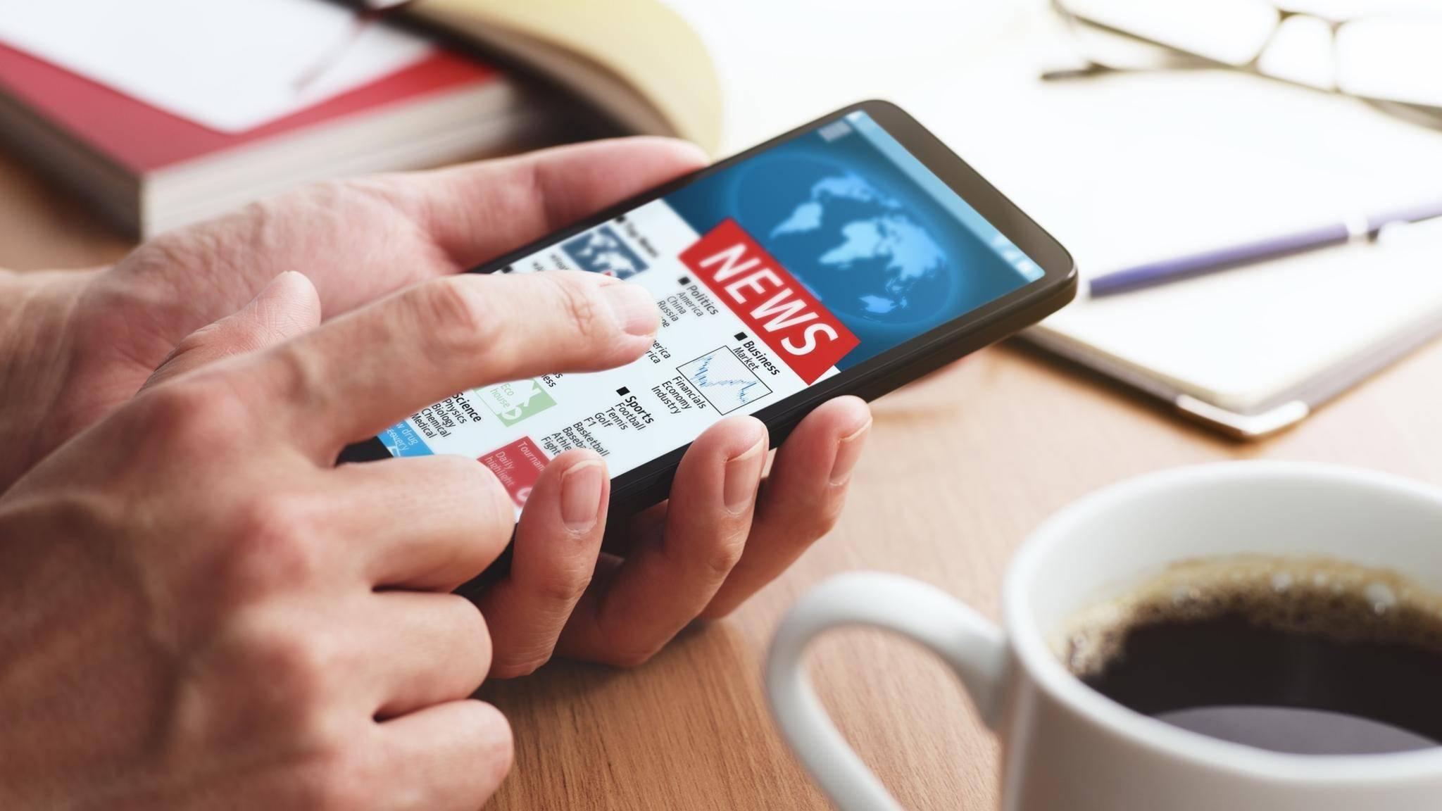 Mann liest Nachrichten-App am Smartphone mit Kaffee.