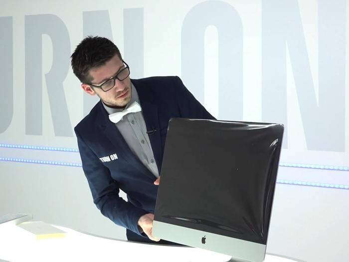 Mit Spannung entfernt Alex die Schutzhülle vom iMac 5K.