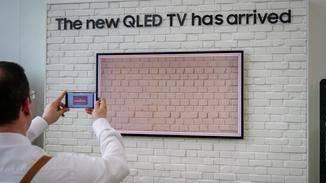 Über das Smartphone wird dann der TV vor dem Hintergrund fotografiert.